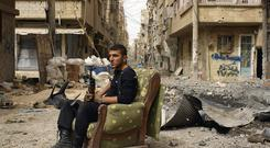 Conflict: A member of the Free Syrian Army holds his weapon as he sits on a sofa in the middle of a street in Deiral-Zor. Photo: Reuters