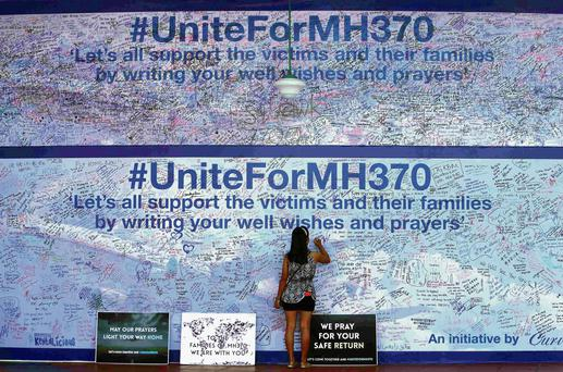 A woman writes a message on the board of hope for Flight MH370