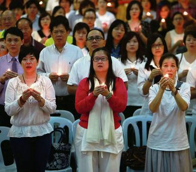 Malaysians hold candles during a special prayer for passengers onboard the missing Malaysia Airlines Flight MH370 at the Chinese Assembly Hall in Kuala Lumpur