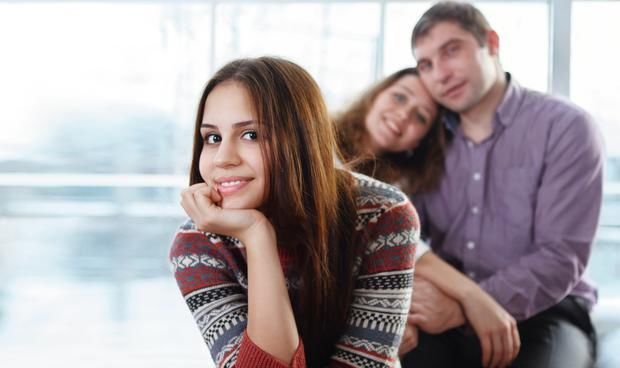 Smiling happy teenage girl sitting in front of her parents
