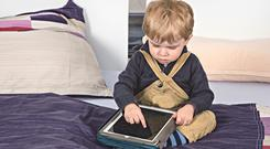 A toddler getting to grips with a tablet. Picture posed