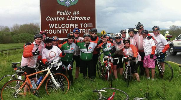 TEAM SPIRIT: Cyclists at the welcome sign in County Leitrim