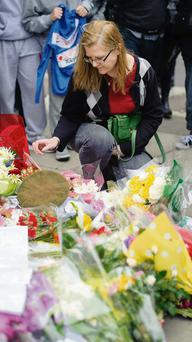 Ingrid Loyau-Kennett, who was praised for her bravery in calmly talking to one of the attackers as he stood clutching a knife with bloodied hands, looks at the floral tributes outside the Royal Artillery Barracks, in Woolwich, east London.