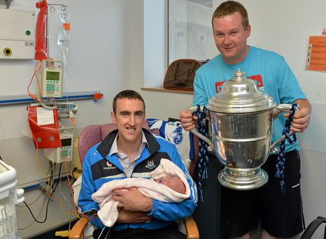 Dublin hurler Peter Kelly holds baby Ella during a visit to Temple Strret as Ella's dad Paul Coffey holds the Bob O'Keeffe Cup