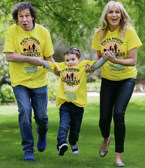 Four year old Oisin McCarton from Lusk takes to the air as he runs with RTE presenter Miriam O Callaghan and actor Stephen Rae, at the launch of the 'Darkness into Light 2014'. Frank McGrath