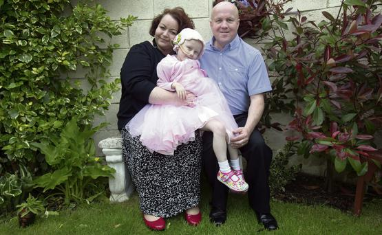 PRETTY IN PINK: Five-year-old Molly McNally, who was diagnosed with Stage 4 Neuroblastoma, with her mum Emma and dad Gerry. With the help of their community and stalwarts of Hill 16, the family are raising funds for Molly's treatment. Photo: Tony Gavin