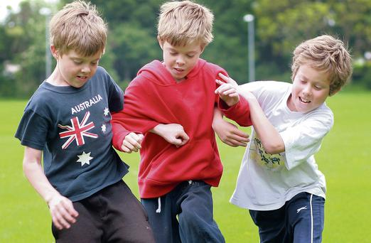 Energy: Grainne's triplets Harry, Luka and Jack playing football in the local park. Photo: Ronan Lang.