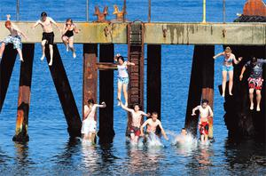 Teenagers enjoying the balmy summer sunshine as they jump off the jetty on Arklow's south beach in Co Wicklow yesterday