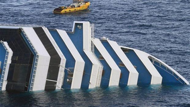 A tug boat floats next to the wreck of the Costa Concordia cruise ship off the coast of the island of Giglio