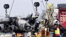 Salvage workers at Cork Airport as the plane's wreckage was lifted from the crash site yesterday. Photo: PA
