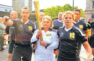 The Olympic Torch is escorted to safety after Dissident Republicans tussled with PSNI Officers near the Peace Bridge in Derry. Photo: PA