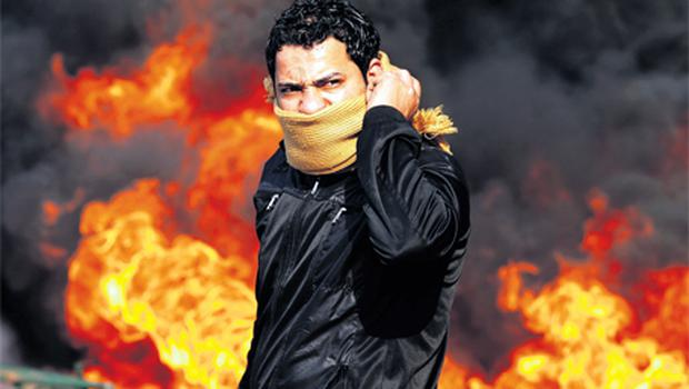 A protester stands in front of a burning barricade during a demonstration in Cairo yesterday