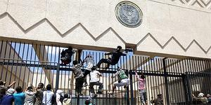 Protesters climb a fence at the US embassy in Sanaa, Yemen