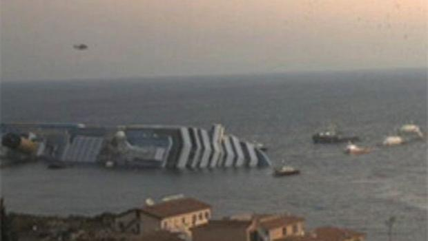 A dawn photograph shows the partly-submerged cruise ship surrounded by rescue vessels