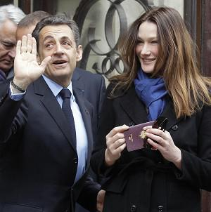 French President and UMP candidate Nicolas Sarkozy and his wife Carla Bruni-Sarkozy leave after casting their votes (AP)