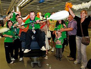 Friends and family of Team Ireland  Special Olympic double medal  winning kayaker Ruairi O'Toole (centre) cheer him home in the arrivals hall of Dublin Airport. Photo: PA
