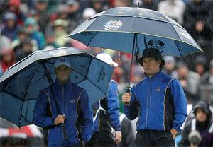 Europe's Martin Kaymer of Germany, left, and Lee Westwood of England shelter under umbrellas on the first hole. Photo: PA
