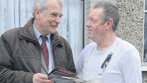 Finian McGrath, the Independent candidate for Dublin North-Central, speaking to painter Anthony Mack while canvassing in Raheny, Co Dublin, yesterday. Photo: Damien Eagers