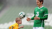 Kevin Doyle keeps a watchful eye as eight-year-old Cian Tormley shows off his skills at the Aviva Stadium yesterday.