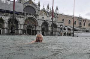 A man enjoys swimming in flooded St. Mark's Square in Venice.