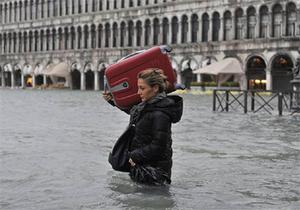 A tourist crosses the flooded St. Mark's Square.