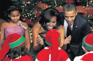 US President Barack Obama, First Lady Michelle Obama and their daughter Sasha greet children at the 'Christmas in Washington' celebration at the National Building Museum in Washington at the weekend