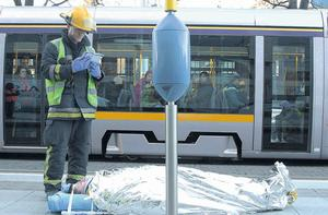A fireman tends to a man injured after a Luas collided with a car in Smithfield, Dublin, yesterday. Photo: STEPHEN COLLINS