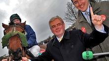 Labour leader Eamon Gilmore addresses the media with Cork South West candidate Michael McCarthy (right) at the All-Ireland road trotting races at Old Chapel, Bandon, Co Cork, yesterday