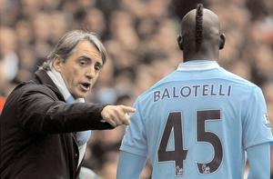 Manchester City manager Roberto Mancini issues instructions to Mario Balotelli during Sunday's defeat against Arsenal