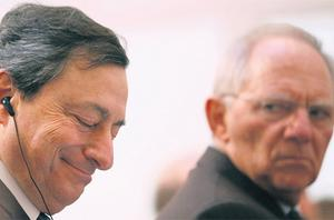 Mario Draghi, president of the European Central Bank, left, listens as Wolfgang Schaeuble, Germany's finance minister, gestures during the 'Ludwig Erhard Lecture' event in Berlin, yesterday