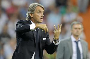 Manchester City's coach Roberto Mancini gives instructions to his players as Real Madrid coach Jose Mourinho watches on