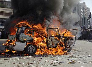 Supporters of the Future Movement gather as they watch the torched vehicle belonging to the Arabic language al-Jazeera satellite television station during a demonstration in Tripoli. Photo: Getty Images