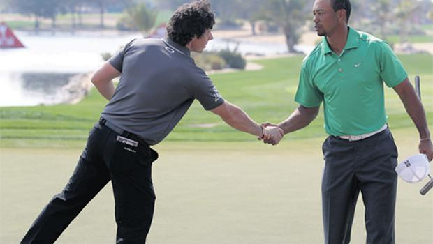 Rory McIlroy and Tiger Woods shake hands on the 18th green after the first round of Abu Dhabi Championship yesterday. McIlroy took the honours on the day shooting five under par to Tiger's two under
