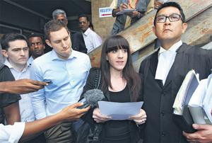 John McAreavey listens as his sister Claire reads a statement outside the court flanked by (far left) Michaela's brother Mark and (right) barrister Dick Sui Wa