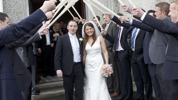 Eoin Kelly and his bride Sarah Maher receive a guard of honour from past and present hurle rs after their wedding.