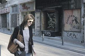 A woman walks in front of closed shops in Athens' main business district yesterday