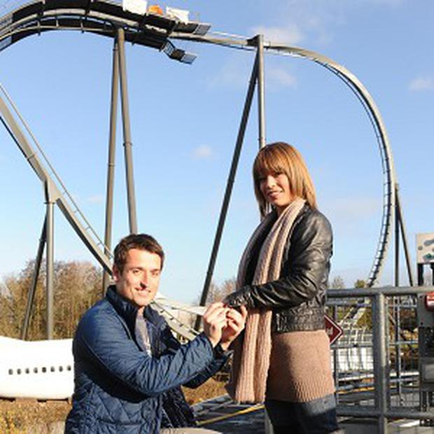 Jon Richards, 26, presents an engagement ring to girlfriend Sarah Jones after he proposed at the top of a 127ft Swarm ride at Thorpe Park (Kate Green/Thorpe Park/PA)