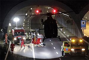 A helicopter takes off from the entrance of the tunnel where the coach crashed in Sierre, western Switzerland