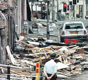 An RUC officer looks at the damage caused by the bomb explosion in Market Street, Omagh