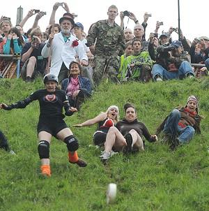 Female competitors chase a cheese down Cooper's Hill in Brockworth, Gloucestershire
