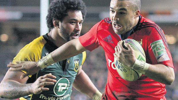 The Munster wing fends off the challenge of Northampton's Samu Manoa