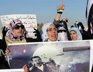 A protester holds a poster featuring a caricature of Syria's President Bashar Al-Assad in Jordan yesterday
