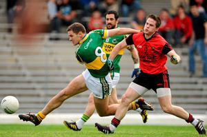 Eoin Brosnan gets in his shot despite the attentions of Paul McComiskey. Photo: Brendan Moran / Sportsfile