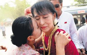 A supporter kisses Aung San Suu Kyi, leader of the National League for Democracy, as she visits polling stations in her constituency. Burmese people voted in the parliamentary elections yesterday, in Kawhmu, Burma