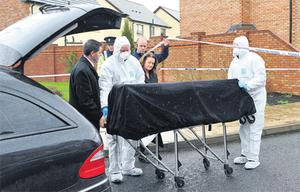 The body of James Hughes is removed from the scene
