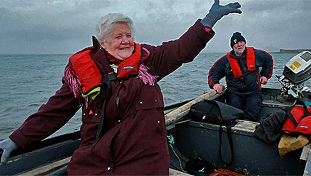 Bridgie O'Malley (82) waves goodbye to friends on Inishbiggle as she sails home to Achill with her son Joe O'Malley after voting