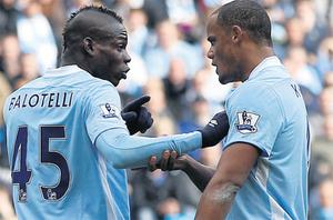 Manchester City captain Vincent Kompany speaks with Mario Balotelli