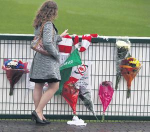A woman reads tributes left at Ravenhill, home of Ulster rugby in Belfast