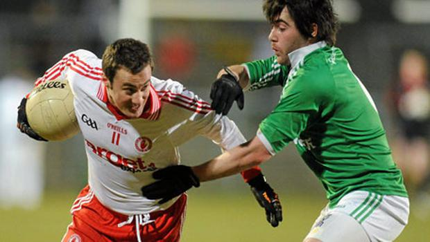 Tyrone's Brian McGuigan tries to get past Barry Mulrone at Brewster Park last night. Photo: Oliver McVeugh / Sportsfile