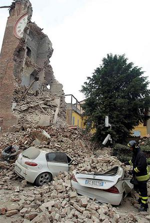 A firefighter stands next to damaged cars in the rubble near the old tower of Delle Rocche castle after an earthquake in Finale Emilia. Photo: Reuters